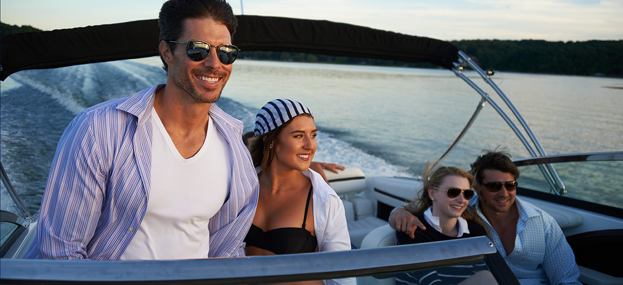 Two Couples on Cobalt Boat Smiling with Wind in their Hair