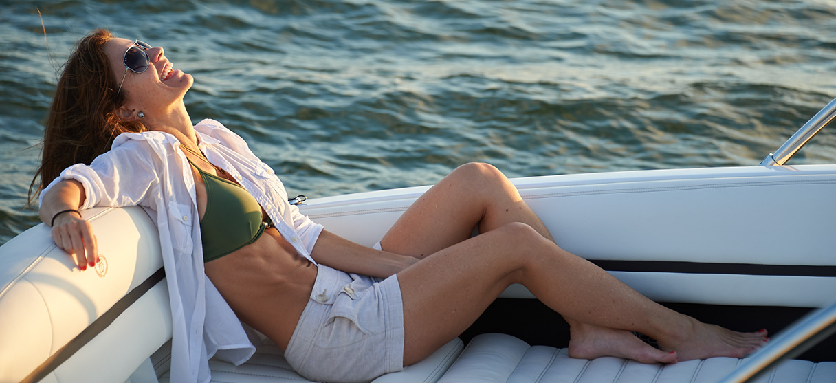 Woman in Green Swimsuit and White Linen Shirt Lounging on Back of Cobalt Boat